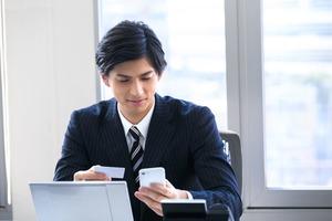 スマホとカード 見比べるビジネスマン