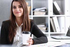 デスクでコーヒーを飲む 女性