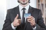 カードを胸に 親指立てる男性