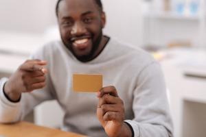 ゴールドカードを指差し見せる男性