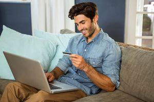 ソファでPCとカードを見る男性
