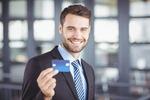 社内でクレジットカードを掲げるビジネスマン男性