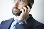 電話で問い合わせているメガネの男性