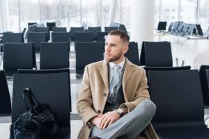 搭乗ゲート前座って待つ男性ビジネスマン