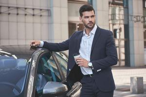 車に乗り込む前コーヒーを持つビジネスマン