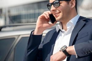 サングラスとスーツ車外で電話する男性