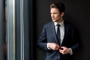 オフィスで窓の外を見るビジネスマン