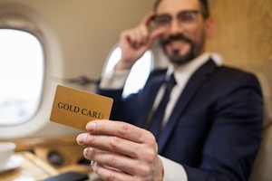 機内でゴールドカードを喜ぶビジネスマン