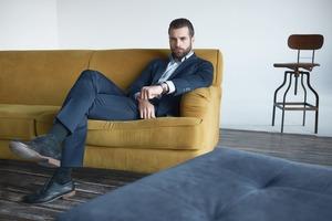 ソファに座り足を組む男性