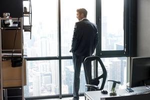 窓からビル下を見つめるビジネスマン