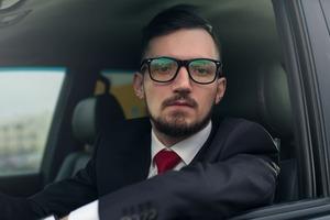 車内から呆然と見ているメガネのビジネスマン