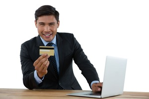 ノートPCをおいてゴールドカードを見せるビジネスマン