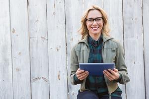 屋外でタブレットを見ながら微笑む女性