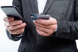 スマホにカード情報を照会するビジネスマンの手