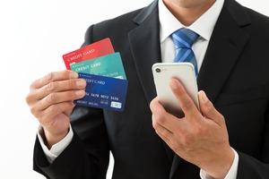 3枚のクレジットカードを持つ男