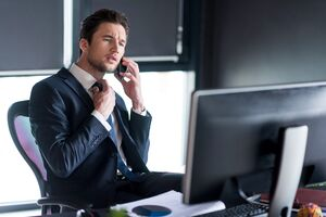 頭を悩ませ電話しながらPCの前にいるスーツ男性