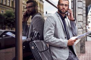 外出先で書類を見ながら電話する男性