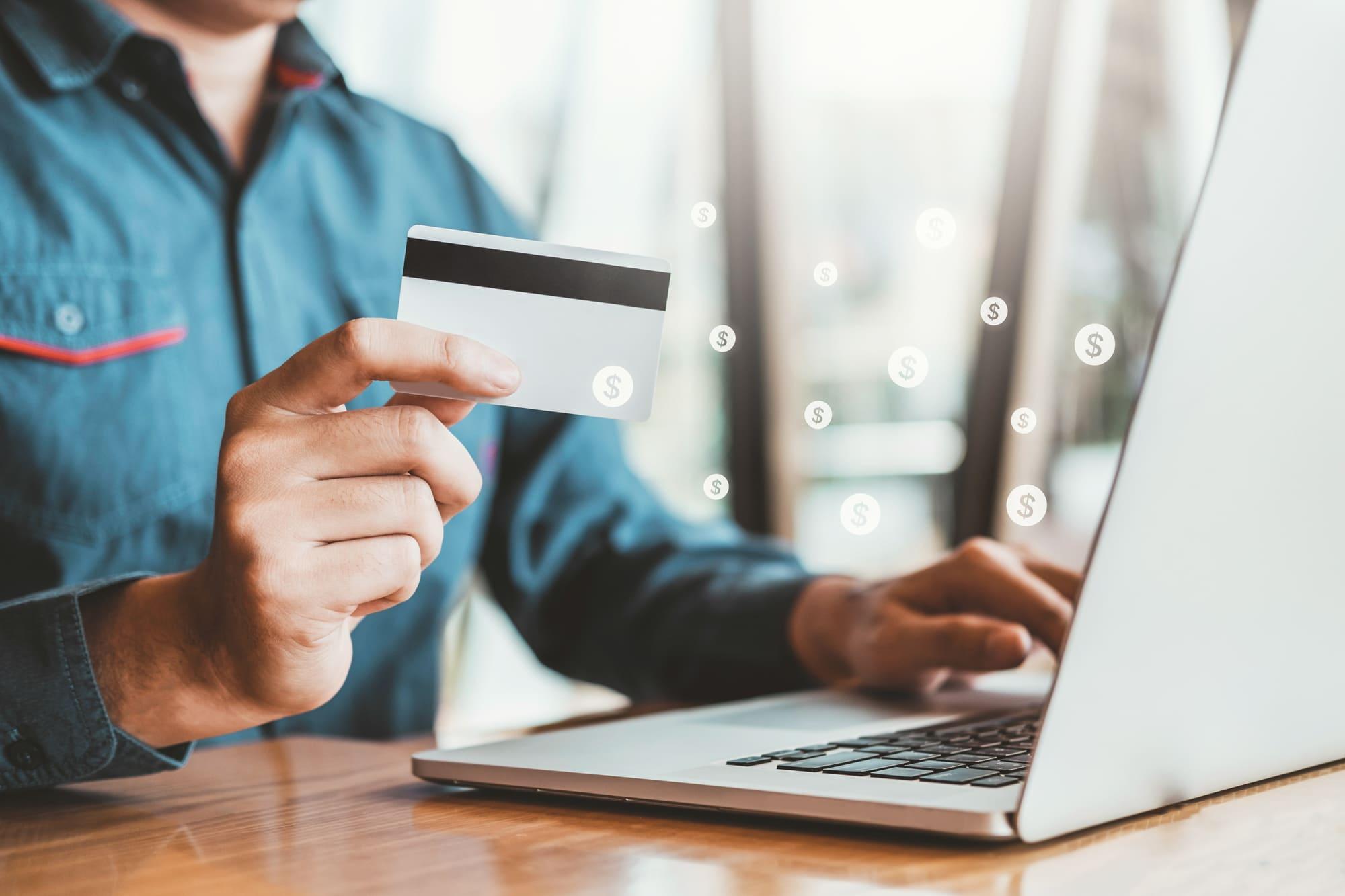 パソコンを開いてクレジットカードを持っている男性