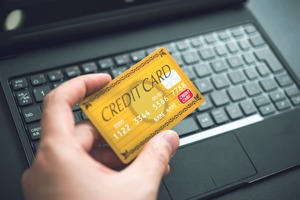 クレジットカードをパソコンの前で持っている
