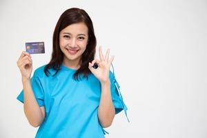 クレジットカードを持ちながらOKサインをする女性