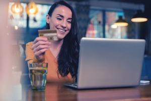 笑顔の女性がクレジットカードを持ちながらパソコンを見ている