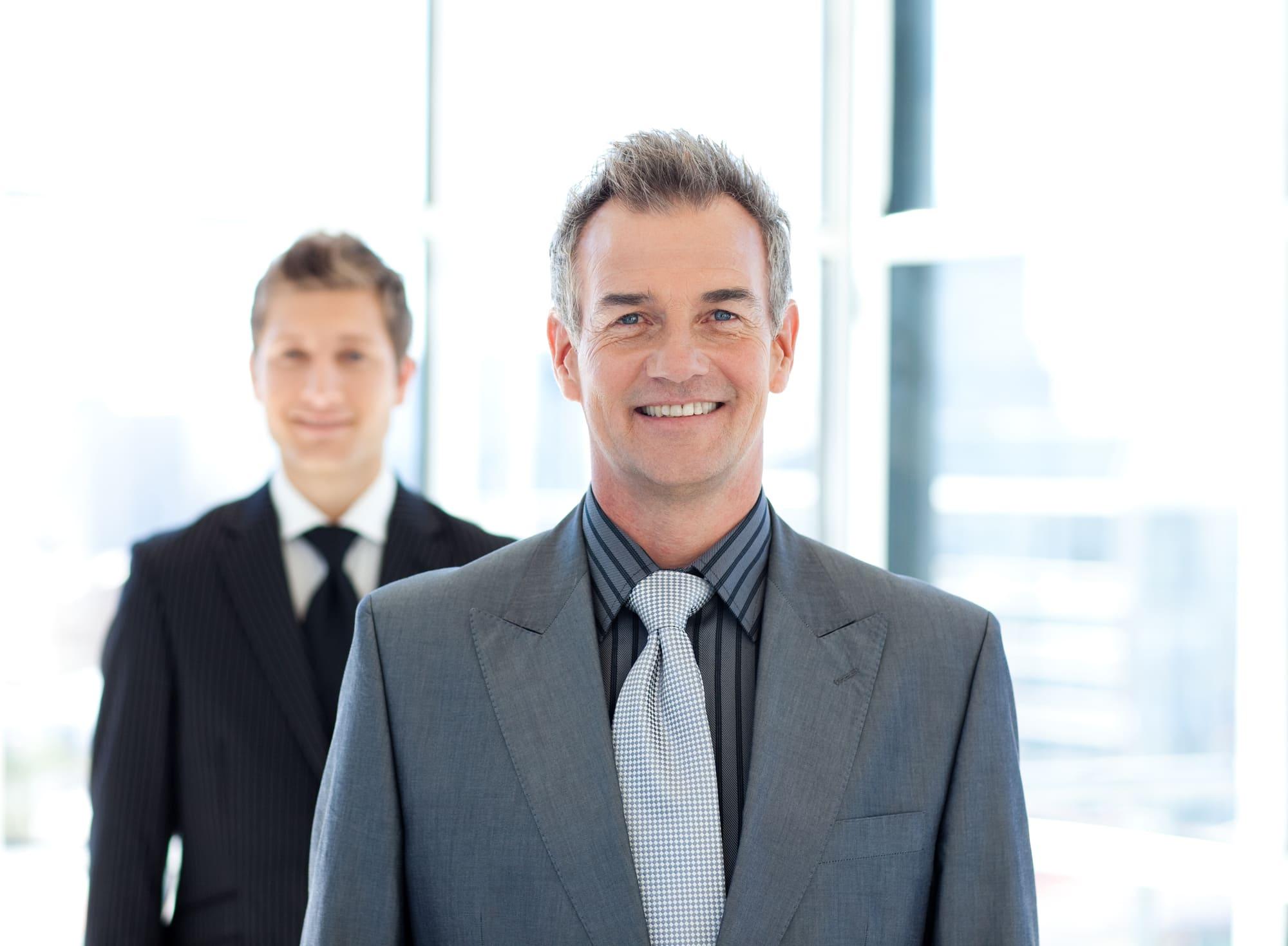来客を迎える社長と補佐の男性