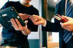 男性がクレジットカードを手渡ししている