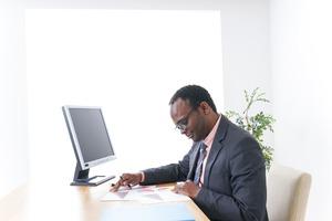 パソコンの前で男性が書類を見ている