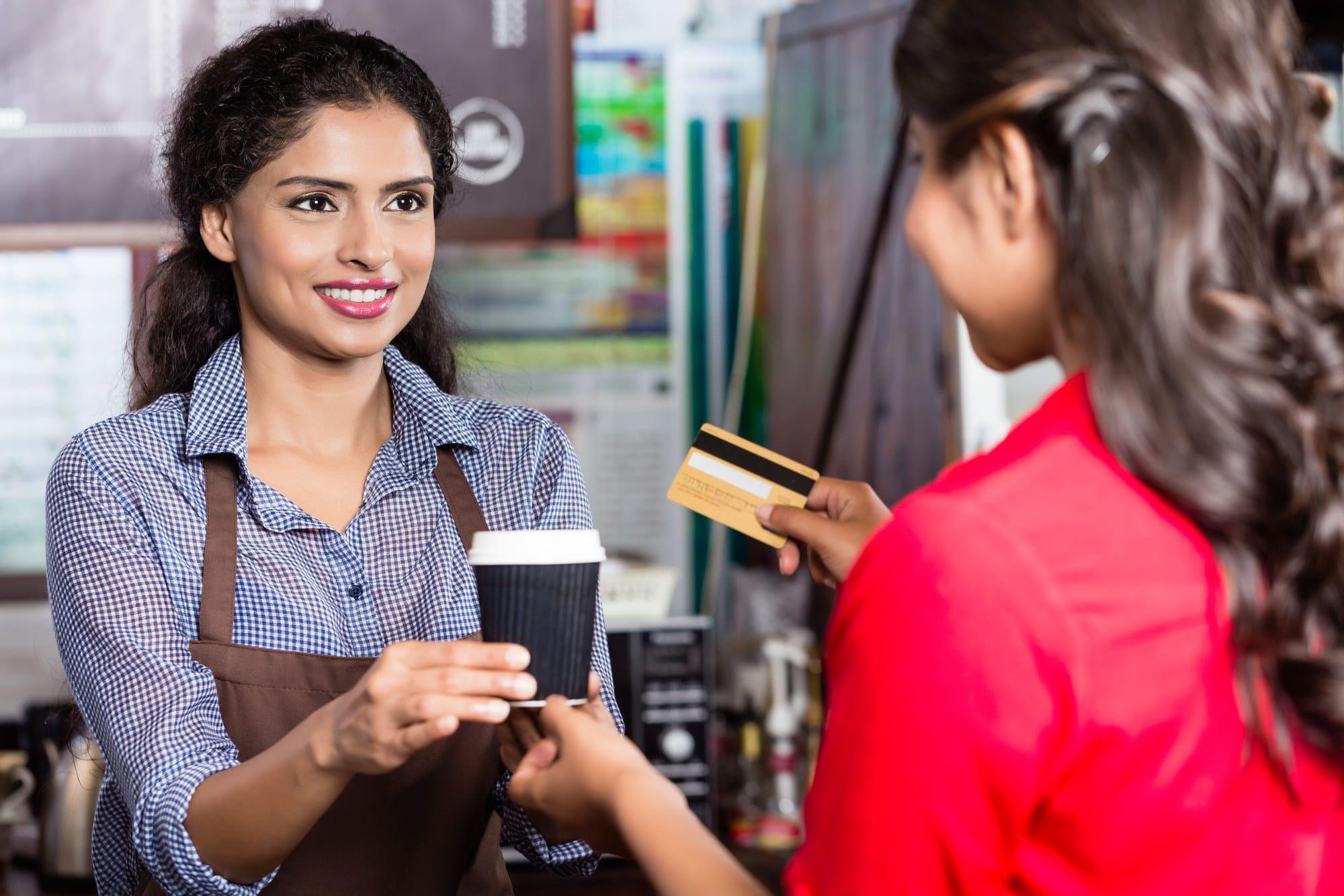 カードでコーヒーを買う女性と女性店員