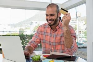 クレジットカードを持った男性がパソコンを見て笑っている