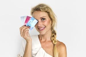 3枚のクレジットカードを持った女性がほほえんでいる